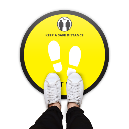 Round floor sticker with a yellow background and the text